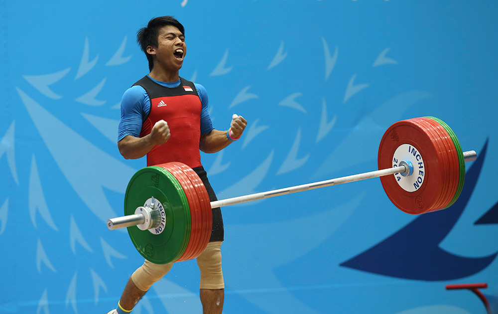 Deni After A Successful Lift In the Men's 69 Kg Weightlifting Competition