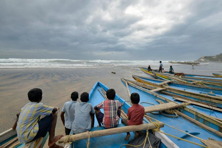 Children sit on fishing boats by the shore before being evacuated, at Visakhapatnam district