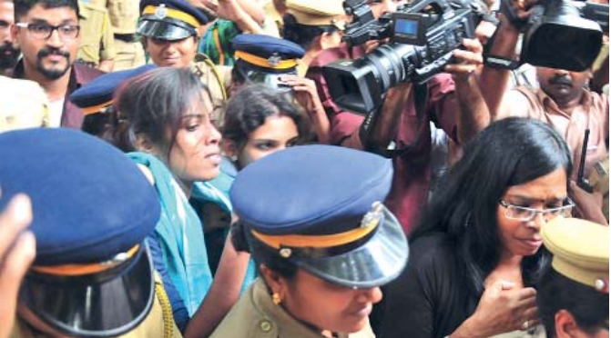 Police arresting kiss of love organizers when they came out of law college to protest